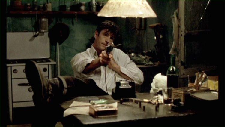 Rupert Everett sitting at a desk, holding a gun in Cemetery Man