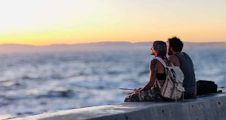 Still from The Cove - Two people looking at the sunset on the sea.