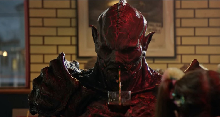 Psycho Goreman sipping on a drink through a straw.