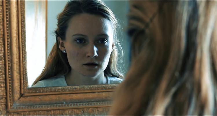 Gwyneth Rhianwen looking at herself in the mirror in Fated.