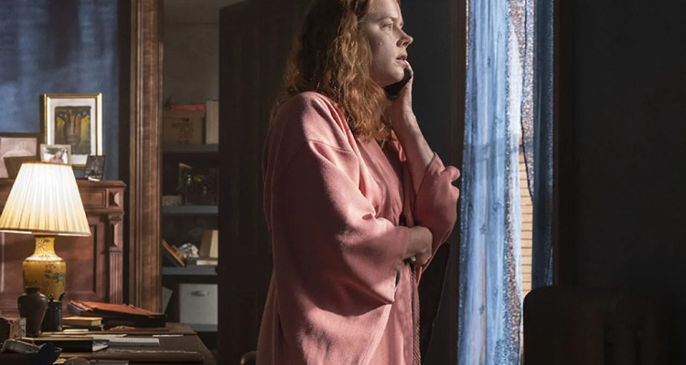 Amy Adams looks out the window while on the phone in The Woman in the Window.