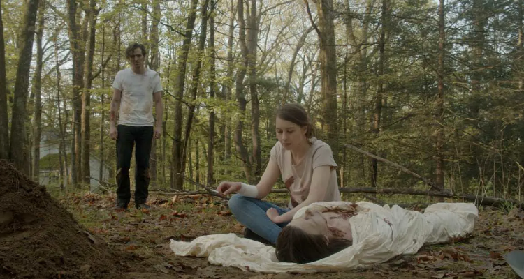 Ava sitting over her sister's body while Jamie looks on - still from An Unquiet Grave