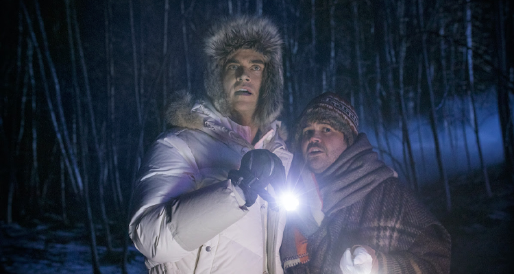 Two men dressed in winter clothes, holding onto a flashlight looking scared.