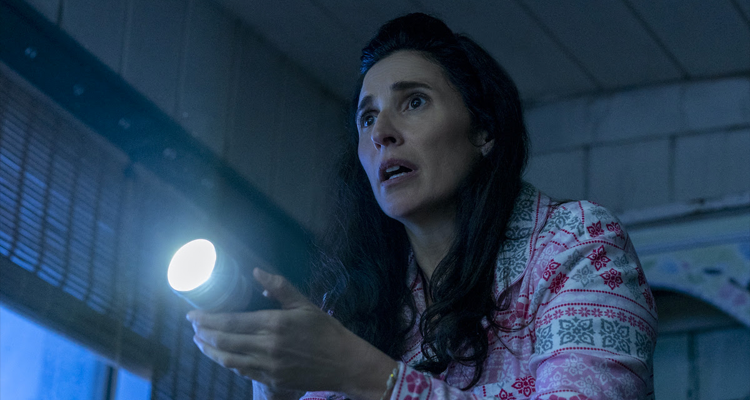A woman holding onto a flashlight and looking scared.