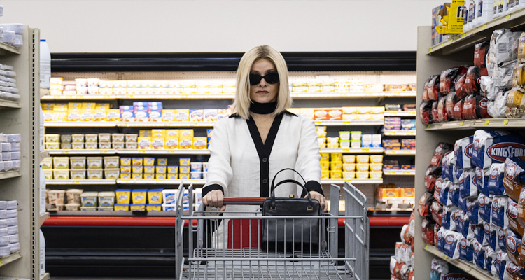 Barbara Crampton walking through a grocery store with sunglasses on.
