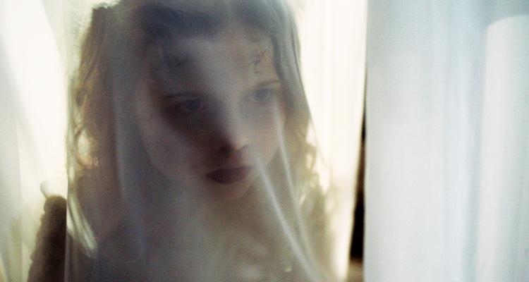 Girl peeking through a sheer curtain. Still from Martyrs Lane.