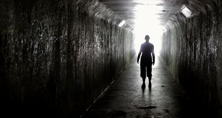 Silhouette of a man in a long, dark tunnel.