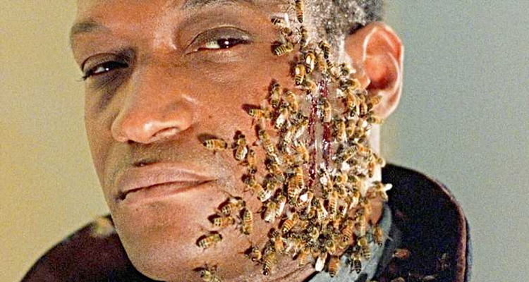 A man with bees covering his face.