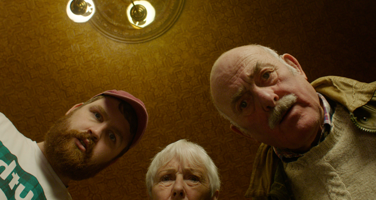 Group of people looking down into the camera. Still from The Nicky Nack.