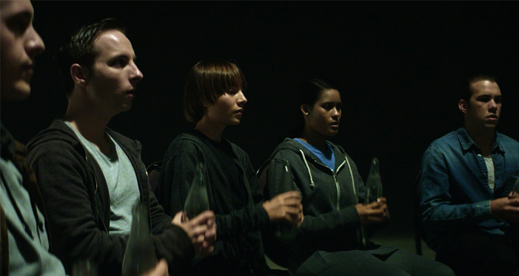 A group of kids, sat in a reverent-like manner, holding glass bottles.