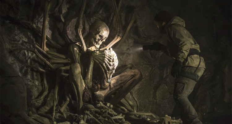 A man shining a torch on a huge skeleton in a cave.