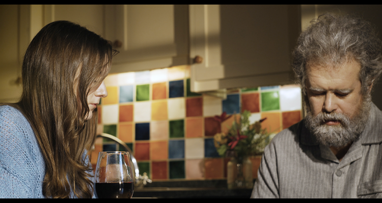 Still from Wastelands. A young woman sits with an older man at a kitchen table.