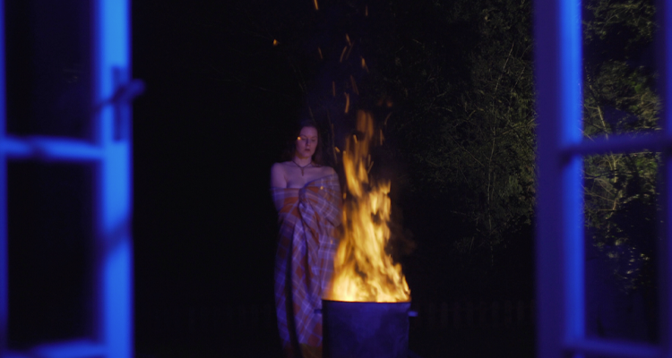 Still from Wastelands. A woman stands outside in front of a burning fire pit.
