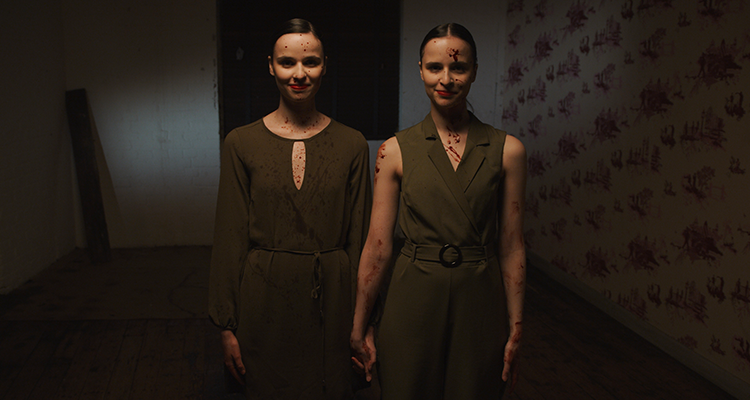 Twin women holding hands and covered in blood looking into the camera smiling.
