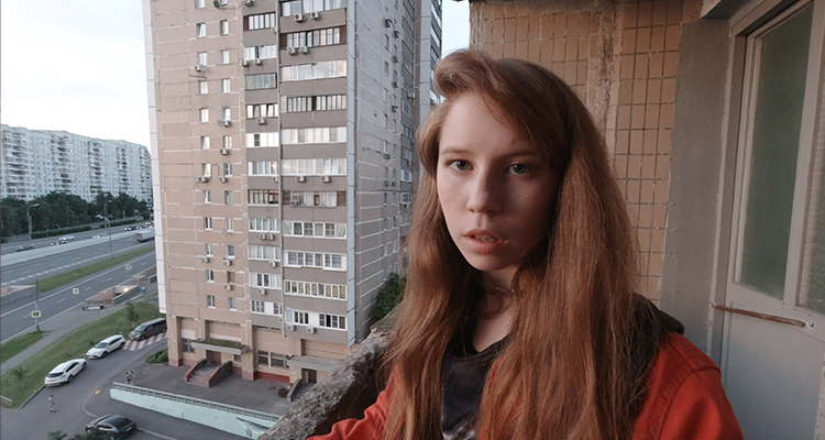 A girl taking a self video with tall buildings behind her. Still from #Blue_Whale.