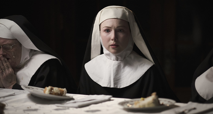 A nun looks solemnly while the others next to her pray. Still from Agnes.