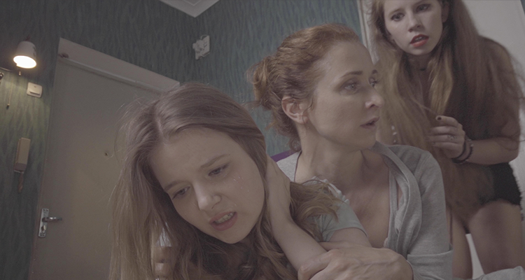 A girl and a woman stand concerned over another girl in the bathroom. Still from #Blue_Whale.
