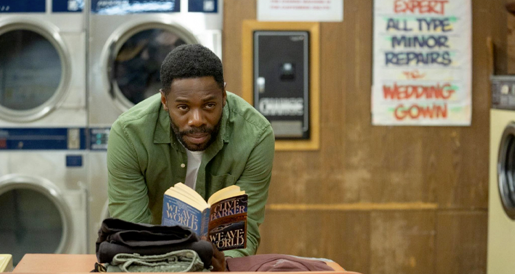 Man standing in a laundromat reading a book. Still from Candyman.
