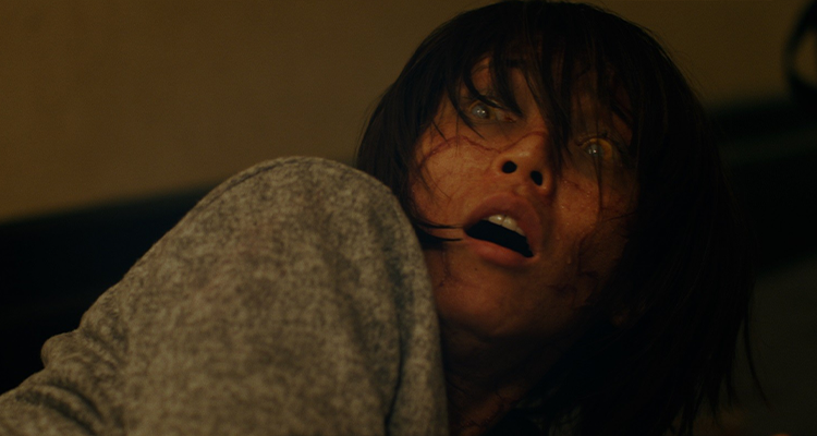 A woman with glazed over eyes and veiny skin looking terrified. Still from Hall.