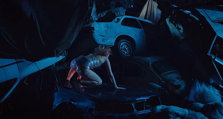 Young boy climbs on a pile of old cars. Still from King Car.