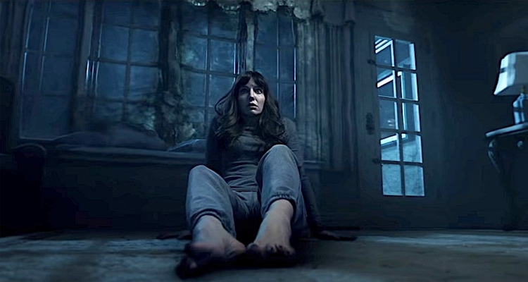 Maddison sitting on the floor of a dark house. Still from Malignant.