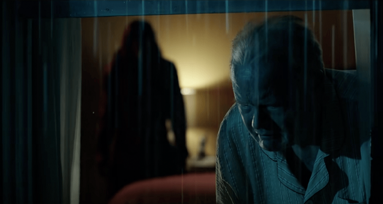 A shadowy figure standing behind a man. Still from Malignant.
