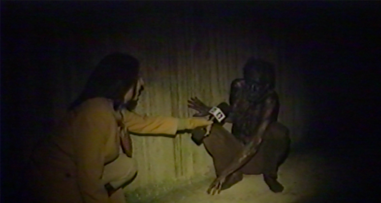 A reporter crouching down to a rat-like man. Still from V/H/S/94