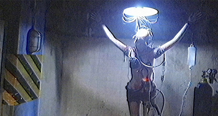 Woman standing tied up in a basement with an IV and wires coming out of her body.