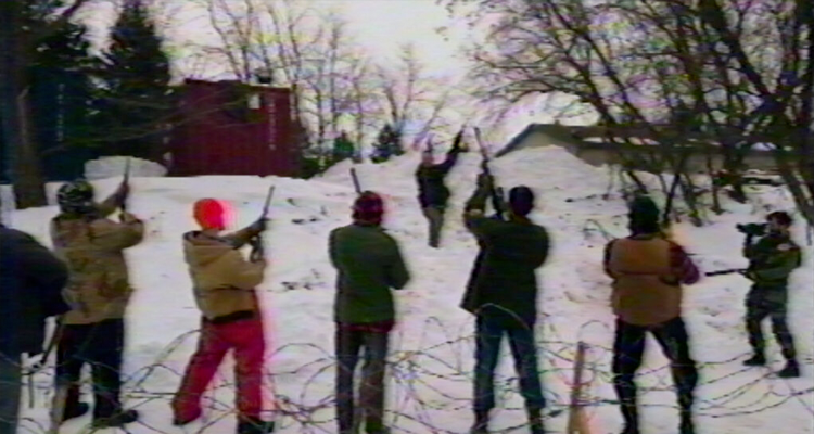 A group of people holding rifles in the air while someone films. Still from V/H/S/94