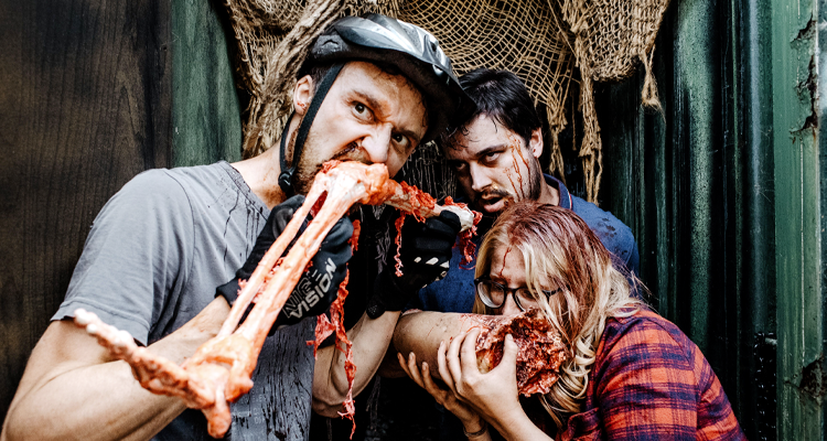 Zombies chewing on a human leg and arm. Still from Zomblogalypse.